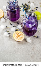 Healthy summer cold beverage, iced organic blue and violet butterfly pea flower tea with limes and lemons, grey concrete background copy space top view