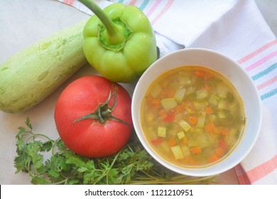 Healthy summer food - Italian seasonal vegetable soup minestrone  with carrot, onions, zucchini, tomatoes, green peas, corn, greens, garlic and bell pepper surrounded by veggies and parsley