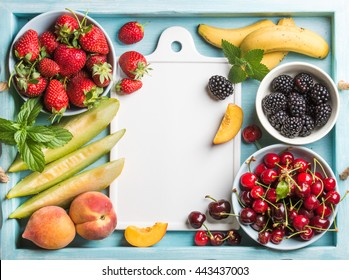 Healthy summer fruit variety. Sweet cherries, strawberries, blackberries, peaches, bananas, melon slices and mint leaves on blue backdrop with white ceramic board in center. Top view, copy space