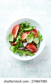 Healthy summer salad with juicy tomatoes, cucumber, lettuce, red onion, spices, fresh rocket and basil. Home made food. Concept for a tasty and healthy vegetarian meal. Wooden background. Top view.