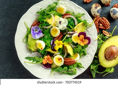 Healthy summer salad with quail eggs, avocado, pecans, wild rocket, red onion and edible viola flowers.