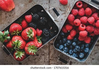 Healthy summer vegan lunch. Flat-lay of fresh seasonal strawberries, raspberries, blueberries and blackberries in lunchboxes over grey background, top view. Vegan, vegetarian, clean eating, detox food