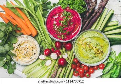 Healthy summer vegan snack plate. Flat-lay of Chickpea, beetroot, spinach hummus dips with fresh vegetables on white background, top view. Clean eating, dieting, vegetarian party food concept