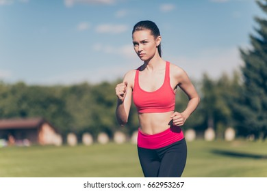 Healthy sunny mood. Young lady athlete is running outdoors, training for marathon run. Beautiful fitness model, in fasionable sports outfit, so focused, fit and fast!