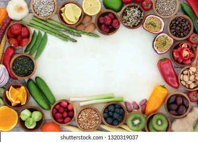 Healthy super food background border on parchment with fresh fish, fruit, vegetables, seeds, grains, nuts, herbs & spices. Very high in antioxidants, anthocyanins, vitamins & dietary fibre. Top view.