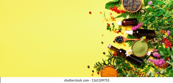 Healthy super food, berries, turmeric, spirulina, omega acid capsules, vitamin c supplement, medicinal herbs and spices on yellow background. Antioxidants concept. Copy space, top view.