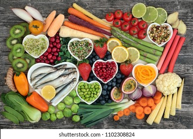 Healthy super food concept with fresh fish, vegetables and fruit in heart shaped dishes and loose. Health food high in omega 3, antioxidants, anthocyanins, minerals, vitamins, Top view.
