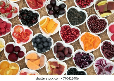 Healthy super food for good health in heart shaped bowls with fruit, vegetable, pulses and grains on rustic  wood background. Superfood high in antioxidants, anthocyanins, vitamins and minerals.