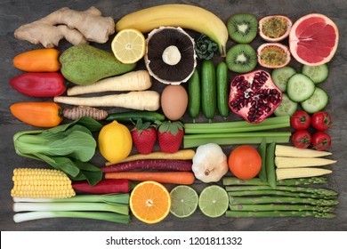Healthy super food selection to promote good health with fresh fruit and vegetables on marble. Foods high in antioxidants, anthocyanins, dietary fibre and vitamins. Flat lay.