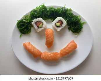 Healthy sushi meal in the shape of a happy face with salmon, avocado, rice and seaweed. A delicious and nutritious Japanese meal.