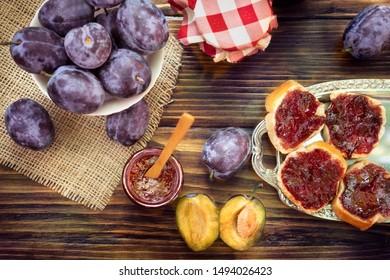 Healthy sweet plum jam spread on bread and in glass jar. Top view of healthy breakfast