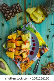 Healthy sweet summer caribbean lunch or dinner with grilled pineapple and shrimps / langoustines on rosemary skewers with greens and avocado on turquoise wooden background top view