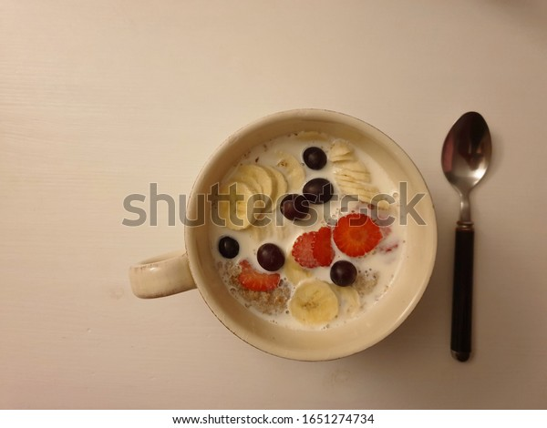 Healthy and tasty breakfast, ready to eat. Weetabix with sliced fruits and milk in the bowl. White wooden table. Top view. Copy space.