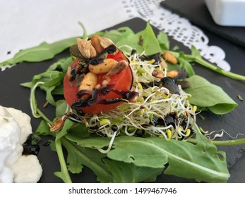 Healthy and tasty Vegan vegetarian lunch at the Spanish restaurant in Sotogrande Andalucia Spain. Herbs, sweet potato, sprouts with tasty spices, pine nuts and sauce. Nice and tasty food.