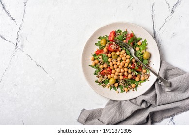 Healthy and tasty vegetarian food. Salad with cooked chickpeas, fresh arugula leaves, chia seeds, cherry tomatoes and green olives on white marble background with copy space