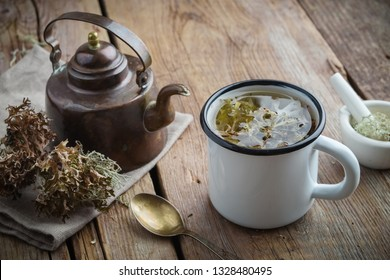 Healthy tea with Iceland moss. Retro tea kettle and mortar on wooden board.