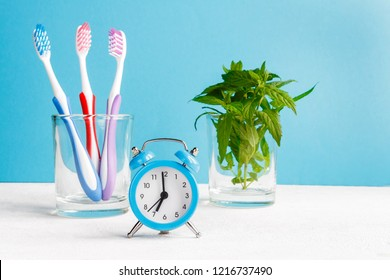 Healthy teeth. Toothbrush  and toothpaste and bath towel and alarm clock on the table in the bathroom  blue background. Regime  day, morning procedures and personal care, health care, health hygiene