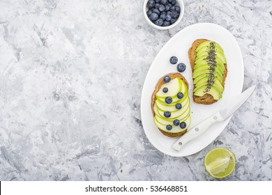Healthy toast with green apple and juicy avocado on a marble background. Color year. Greenery. Top