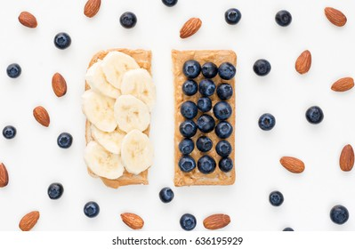 Healthy toast snack with whole wheat bread, creamy peanut butter banana and blueberries isolated on white. Healthy eating, dieting concept
