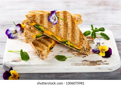 Healthy toasts with avocado, cheddar cheese and tomatoes for breakfast or lunch. Vegetarian sandwiches. Plant-based diet. Whole food concept.