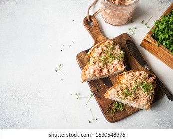 Healthy toasts with salmon pate and fresh green sprouts on yeast-free bread on wood cutting board on grey background. Copy space