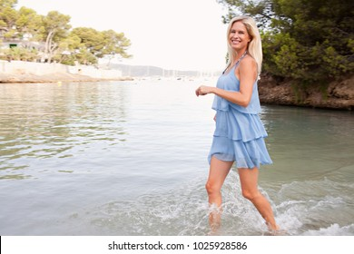 Healthy tourist middle age beautiful woman running on sea on summer holiday splashing water, looking smiling joyful on beach, outdoors. Fun summer travel, wellness active leisure recreation lifestyle.