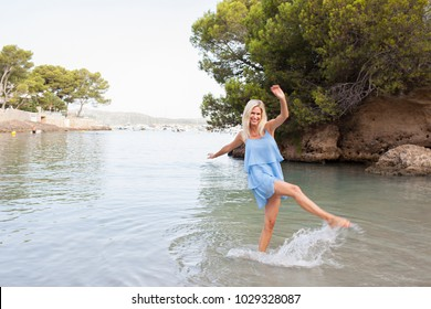 Healthy tourist middle age beautiful woman kicking water on sea shore, summer holiday splashing, looking and smiling joyful on beach, outdoors. Fun travel wellness active leisure recreation lifestyle.