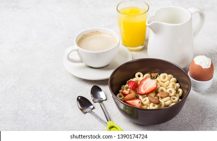 Healthy traditional breakfast. Whole grain rings cheerios, coffee, orange juice and egg on table.