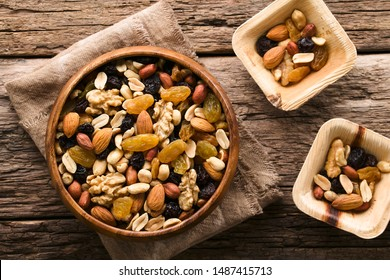 Healthy trail mix snack made of nuts (walnut, almond, peanut) and dried fruits (raisin, sultana) in wooden bowl, photographed overhead (Selective Focus, Focus on the trail mix in the big bowl)