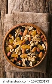 Healthy trail mix snack made of nuts (walnut, almond, peanut) and dried fruits (raisin, sultana) in wooden bowl, photographed overhead (Selective Focus, Focus on the trail mix)