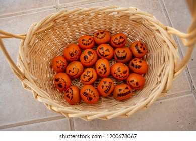 healthy treat for Trick or Treat Halloween snacks for kids - basket of Mandarin oranges with hand-drawn Jack o Lantern faces in black marker pen