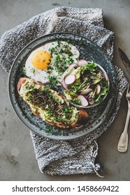 Healthy trendy breakfast plate. Flat-lay of avocado toast on sourdough bread with herbs and sprouts, fried egg with coriander and salad over grey concrete background, top view. Clean eating concept