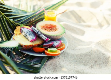 Healthy Tropical fruits assortment on  plate with fresh juice,  summer beach background.