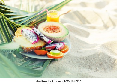 Healthy Tropical fruits assortment on plate with fresh juice, summer beach background