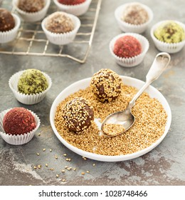 Healthy truffles with dates and nuts covered in sesame seeds, strawberry and matcha powder