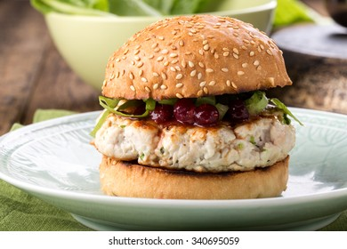 Healthy turkey burger on a bun with cranberry sauce