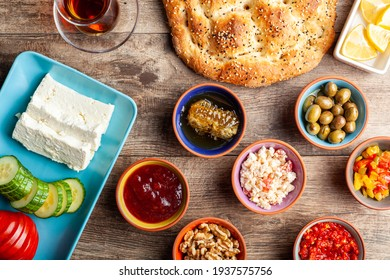 Healthy Turkish breakfast, with sliced tomato, cucumber, and white feta cheese, small bowls of strawberry jam, olive, honey, pepper paste. Tea is served in traditional Turkish tea glass. Ramadan feast