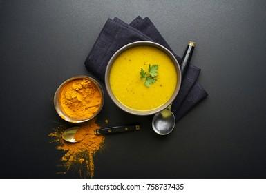 Healthy turmeric or curcuma cream soup on black background