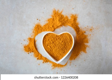 Healthy turmeric powder in a white heart shaped bowl.