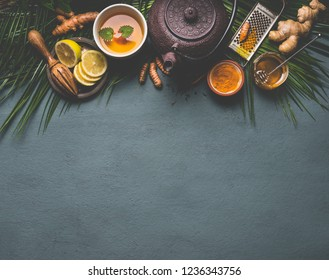 Healthy turmeric spice tea with lemon,  ginger and honey on dark background with copy space for your design, top view, border. Immune boosting remedy , detox and dieting concept