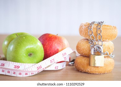 healthy or unhealthy eating lifestyle concept choosing between apples with measuring tape and donuts with chain and lock
