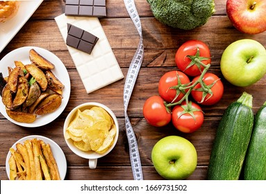 Healthy and unhealthy food concept. Fruit and vegetables vs sweet and potatoe fries top view flat lay on rustic background