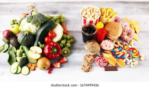 gesunde oder ungesunde Lebensmittel. Concept photo von gesunden und ungesunden Lebensmitteln. Obst und Gemüse vs. Donuts, Süßigkeiten und Burger auf dem Tisch