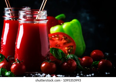 Healthy and useful spicy smoothies or juice from red tomatoes and bell peppers with green basil in glass bottles on a dark background, selective focus