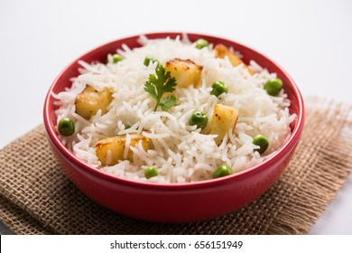 Healthy Veg Pulav OR Pilaf using Paneer, Green Peas and Basmati Rice. Served in a bowl over moody background. selective focus