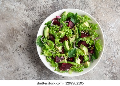 healthy vegan avocado and beet salad in white  bowl, top view
