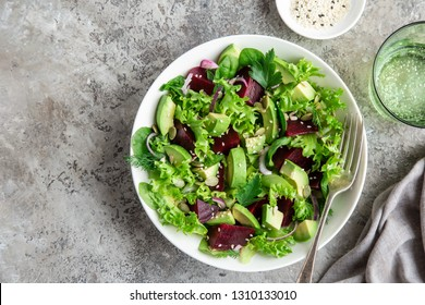 healthy vegan avocado and beet salad in white  bowl, top view, copy space