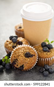 Healthy vegan banana blueberry muffins with coffee in a paper cup to go