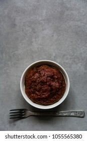 Healthy vegan beetroot muffin in white cup and vintage fork on rustic grey board. Festive composition, copy space available. Flat lay. Film style.
