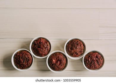 Healthy vegan beetroot muffins in white cups on wooden background. Festive composition, copy space available. Flat lay. Matte effect.